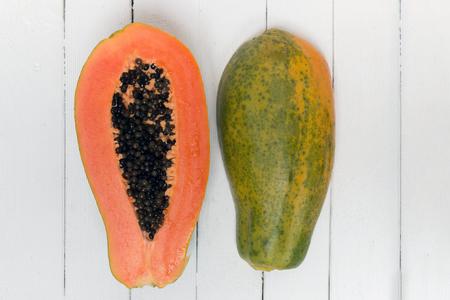 Fresh tropical papaya fruit isolated on a white wooden background.