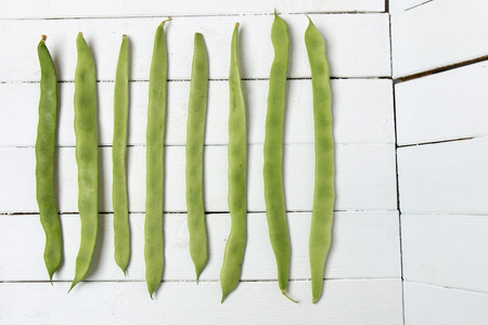 snap bean: Close view of a bunch of common beans on a white wooden background. Stock Photo