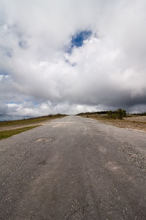 rough road: Long rough mountain asphalt secondary road with a cloudy sky.