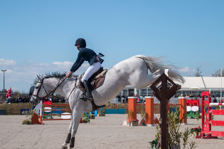 Athlete performing on a horse obstacle jumping competition. Editorial