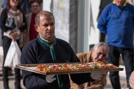 OLHAO, PORTUGAL - DECEMBER 2015: A special day where chef Filipe Martins from Kubidoce creates a giant Bolo Rei (King cake), the portuguese Christmas cake. In the end is offered to people in the street, if you like you can donate money to local associatio