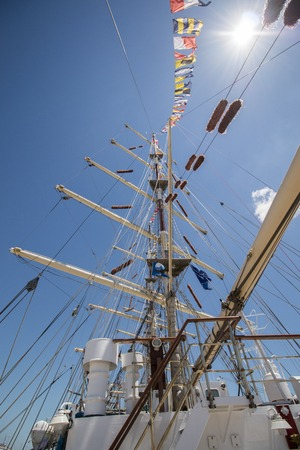 View of majestic Tall Ship with sails with a cloudy sky.