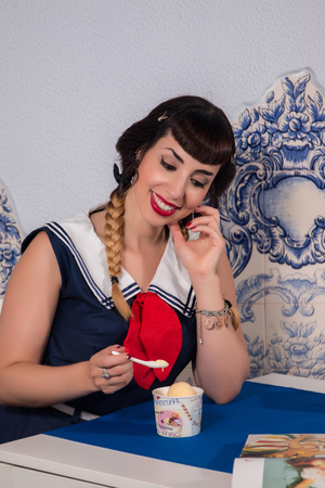 Cute pinup girl on a sailor dress in  a typical portuguese restaurant. Stock Photo