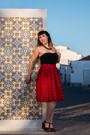 Cute and fashionable pinup girl walking on the street. Stock Photo