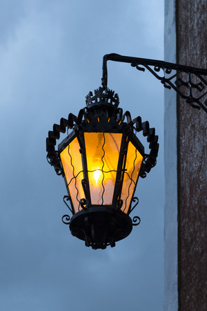 View of a lit classic European streetlight design.