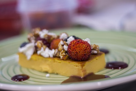 Close view of a gourmet dish of ricotta and pumpkin sweet cake, decorated with several fruits and cereals.