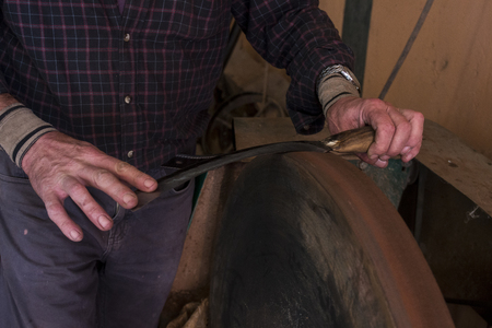 sharpening process: Close view of a worker sharpening a cork knife.