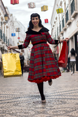 Cute and happy pinup girl goes shopping in Christmas on the streets of Faro, Portugal. Stock Photo