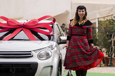 View of a happy pinup girl next a new car wrapped with a red ribbon. Stock Photo