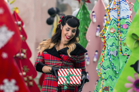 View of a colorful and cute christmas pinup girl with presents. Stock Photo