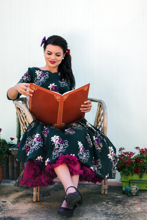 Menina retro vintage lendo um grande livro Foto de archivo