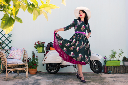 Vintage girl with beautiful floral dress next to a classic motorcycle. Stock Photo