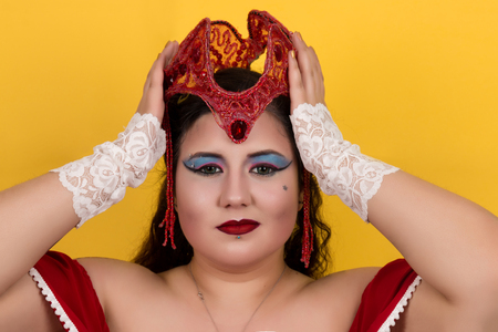 View of pinup vintage girl holding a red fantasy crown over a yellow background. Stock Photo