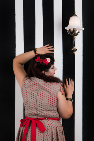 Pinup girl posing on a black and white stripes backdrop.
