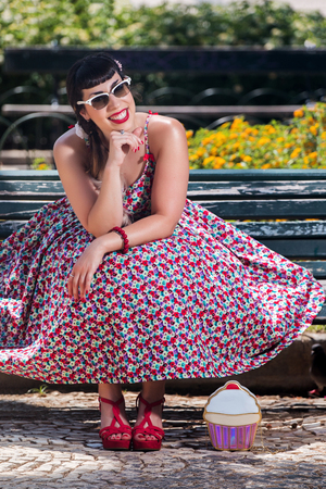 Pinup girl  with dress relaxing in the beautiful urban park. Stock Photo