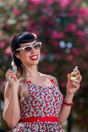 Pinup girl applying perfume in a beautiful urban park.