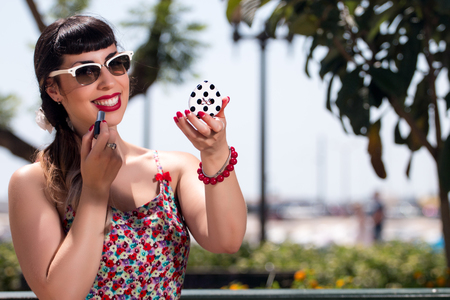 Pinup girl applying lipstick in a beautiful urban park.