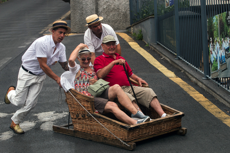 FUNCHAL, MADEIRA - 19th JUNE, 2017: Traditional toboggan men operating a wicker basket car with tourists. Editorial