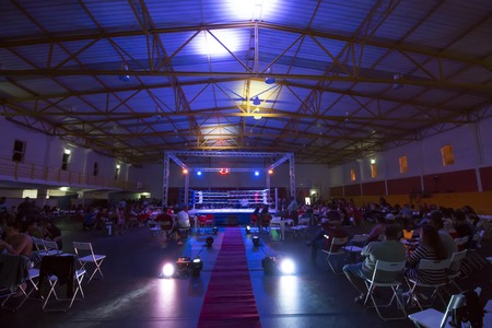 Wide view of a kickboxing event inside a warehouse.