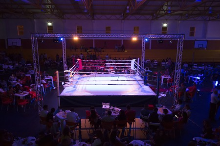 Wide view of a kickboxing event inside a warehouse. Stock Photo - 89735816