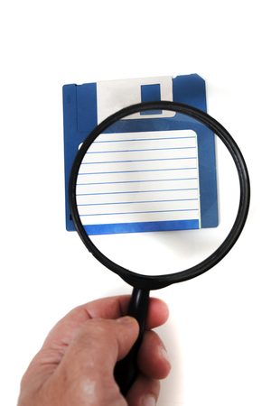 hand with magnifying glass inspecting on floppy disk concept.