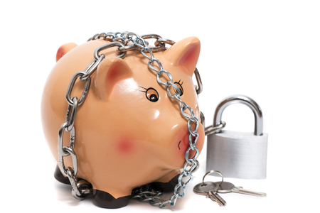 Close up view of a cute pink piggy bank with lock isolated on a white background.
