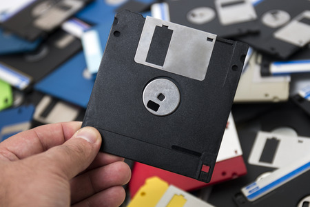 hand grabs a floppy disk from a big pile on the background.