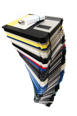 Vertical pile of computer floppy disks with usb disk isolated on a white background.