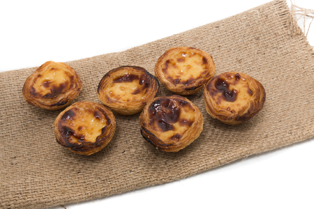 Famous Portuguese egg pastry tart called Pastel de Belem on hessian fabric.