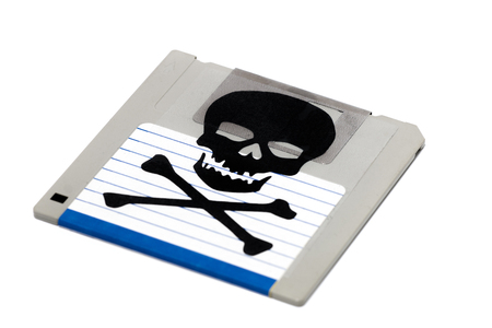 Close up view of a infected computer floppy disk isolated on a white background. Conceptual image with skull and bones. 写真素材