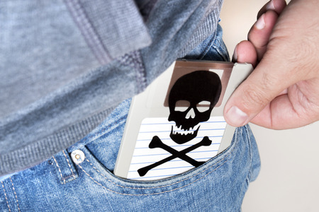 Man with infected floppy disk on pocket. Conceptual image with skull and bones. 스톡 콘텐츠
