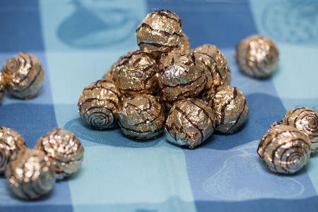 Pile of sweet round chocolate candies for christmas celebrations on a table cloth.