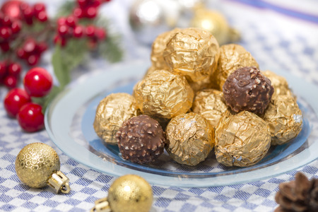 Chocolate candy balls wrapped on beautiful golden paper with xmas ornaments. Stock Photo