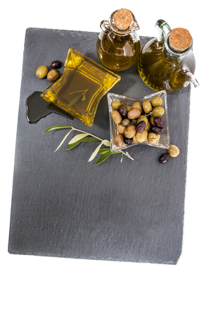 Green and black olives with olive oil bottles isolated on a white background.