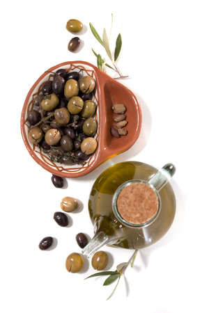 Green and black olives with olive oil bottle isolated on a white background. Stock Photo