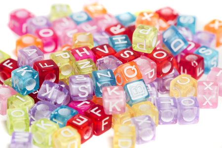 Colorful plastic beads with letters isolated on a white background. Stock Photo