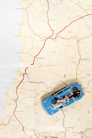 Travel concept of a vintage beetle with surf board on a map. Editorial