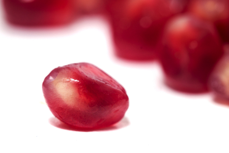Close up view of tasty pommegranate fruit seeds isolated on a white background.