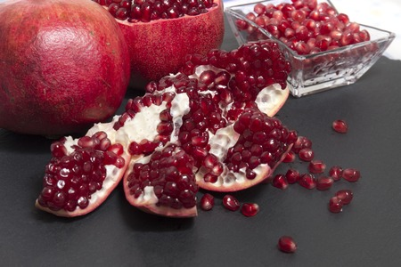 Close up view of tasty pommegranate fruit on top of a slate stone. Stock Photo