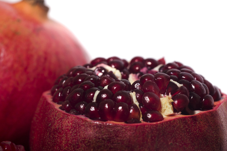 Close up view of tasty pommegranate fruit isolated on a white background.