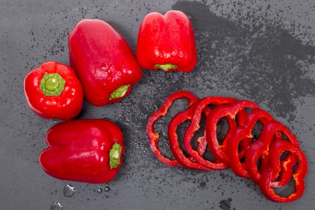 red bell peppers on a black stone of schist, wet and sliced.
