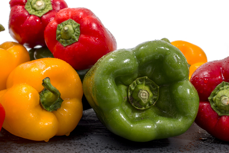 colorful bell peppers on a black stone of schist.