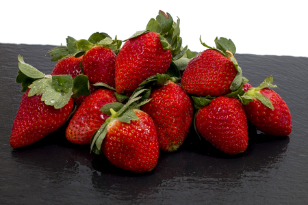 Red tasty strawberries on a black slab of schist. Stock Photo
