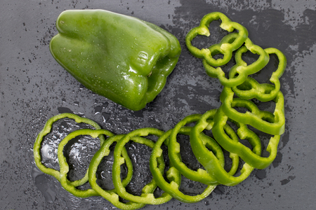 green bell peppers on a black stone of schist, wet and sliced.