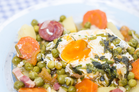 Traditional portuguese culinary meal of green peas with egg, potatoes and carrots.