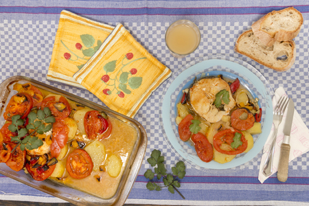 Traditional portuguese meal of fish with potatoes and tomato, made on the oven.