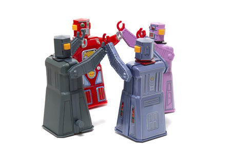 Vintage tin robot toys connected on a circle meeting. Stock Photo