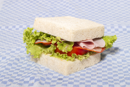 sandwich with ham over a blue cloth.