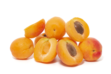 View of tasty Armenian plums (Prunus armeniaca) over a white wooden background.