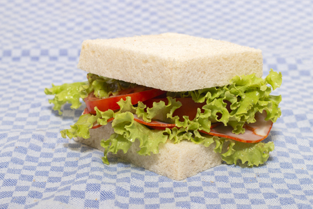 sandwich with paio sausage over a blue cloth. Imagens